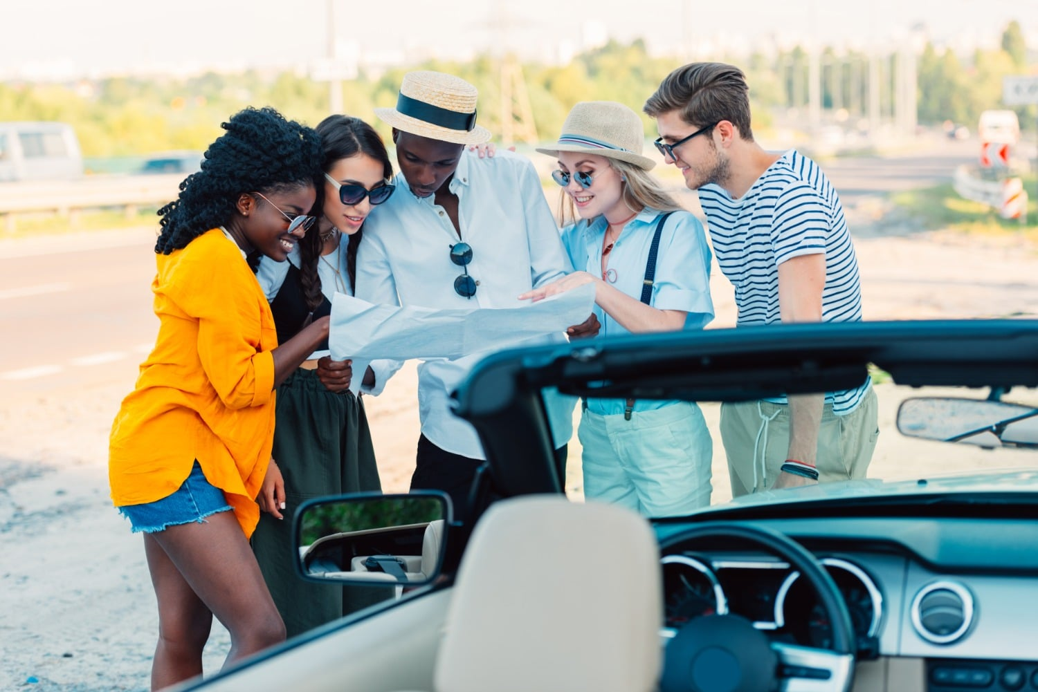 Group of young adults huddled around map behind convertible car