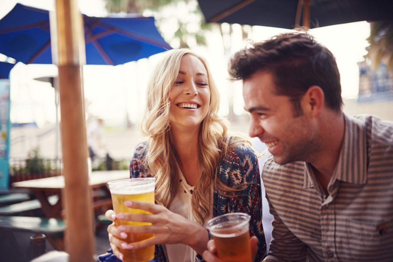 woman and man smiling holding beer outside on patio