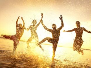 golden backlit silhouettes of people splashing in shallow water