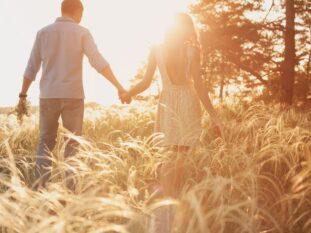 Couple walking through field, sun rays